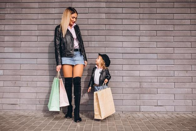 Mère avec sa petite fille mignonne avec des sacs Photo gratuit