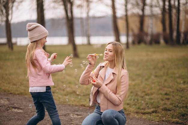 Mère avec sa petite fille soufflant des bulles Photo gratuit