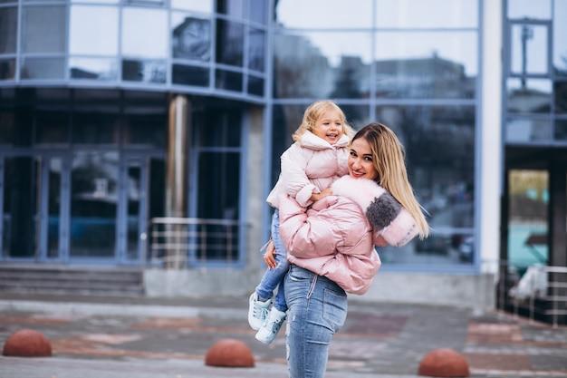 Mère avec sa petite fille vêtue d'un linge chaud en dehors de la rue Photo gratuit