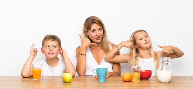 Mère avec ses deux enfants prenant son petit déjeuner et faisant un geste de téléphone Photo Premium
