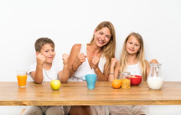 Mère avec ses deux enfants prenant son petit déjeuner et faisant le geste de la victoire Photo Premium