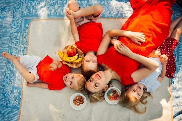 Mère et ses enfants couchés sur une couverture Photo gratuit