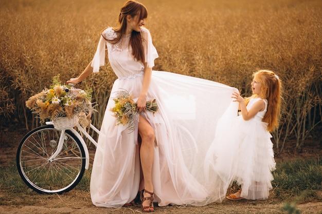 Mère avec son enfant dans de belles robes à vélo Photo gratuit
