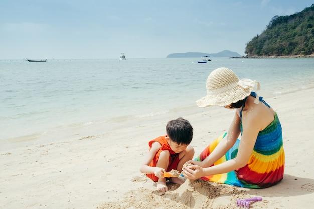 Une mère et son fils sur la plage en plein air mer et ciel bleu Photo Premium