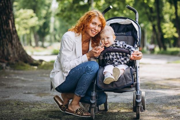 Mère Avec Son Petit Fils Dans Un Landau Dans Le Parc Photo gratuit