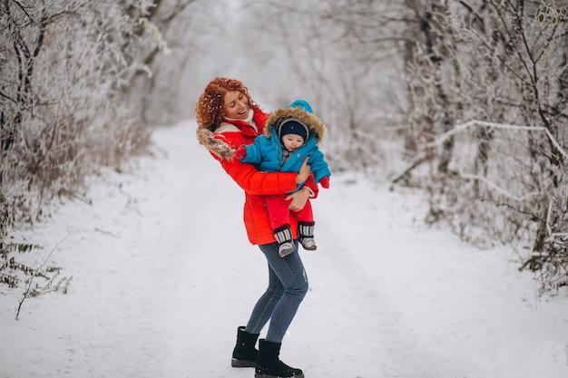 Mère avec son petit fils ensemble dans un parc d'hiver Photo gratuit