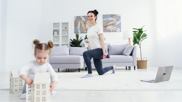 Mère Sportive Faisant Des Exercices Avec Des Haltères Et Sa Jolie Fille Tendre Jouant Avec Des Jouets Au Premier Plan. Photo Premium