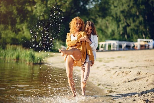 Mère sportive avec jolie fille marchant près du lac Photo gratuit