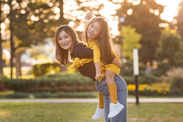 Mère Tenant Sa Fille Sur Son Dos Photo Premium