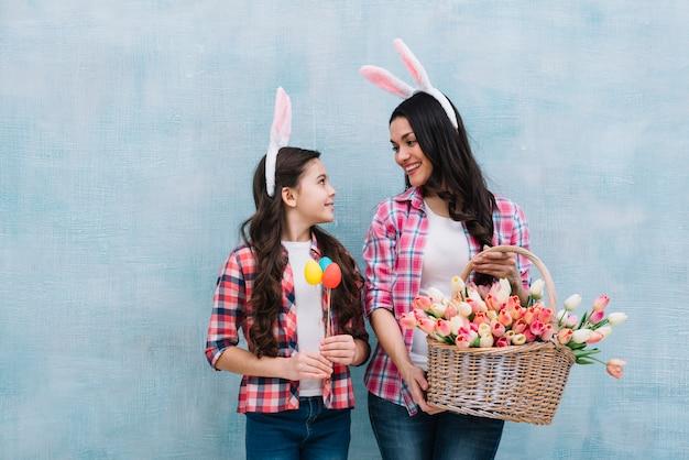 Mère, tenue, panier tulipes, regarder, fille, tenant, oeufs pâques, dans, main, contre, fond bleu Photo gratuit