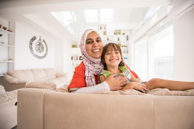 Mère traditionnelle musulmane avec petit fils mignon à la maison dans le salon Photo Premium