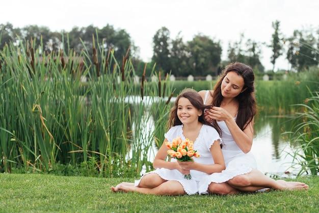Mère, tressage, cheveux, fille, bord lac Photo gratuit