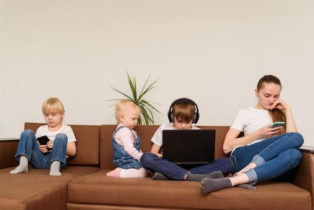 Mère Et Trois Enfants Sont Assis Sur Un Canapé Et Utilisent Un Téléphone Et Un Ordinateur Portable. Dépendance Aux Personnes Et à La Technologie Photo Premium