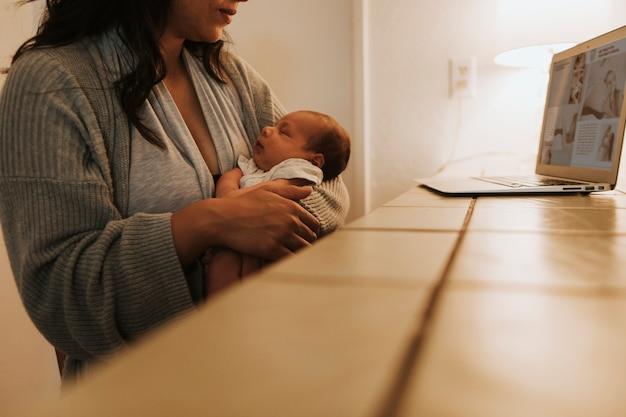 Mère utilisant un ordinateur et tenant son bébé Photo Premium