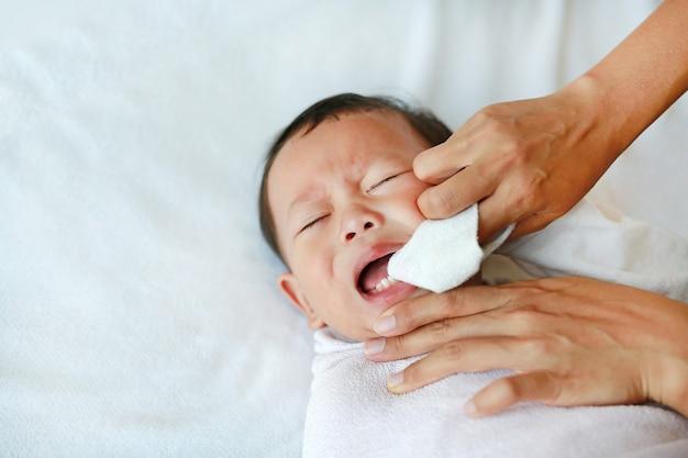 La mère utilise un doigt pour nettoyer la langue et les dents du bébé avec une gaze propre. Photo Premium
