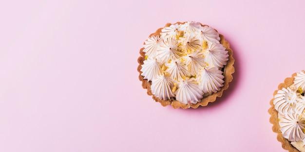 Meringue italienne sur des tartelettes sur fond rose pâle Photo gratuit