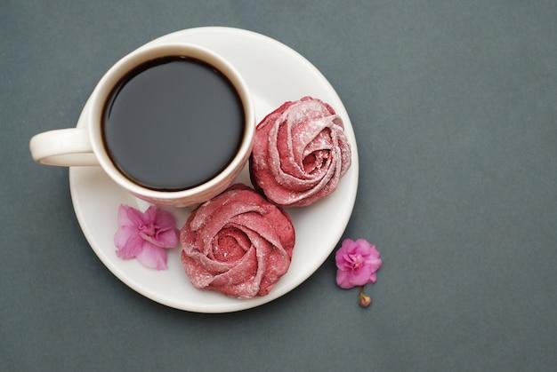 Meringues roses et tasse de café. Photo Premium
