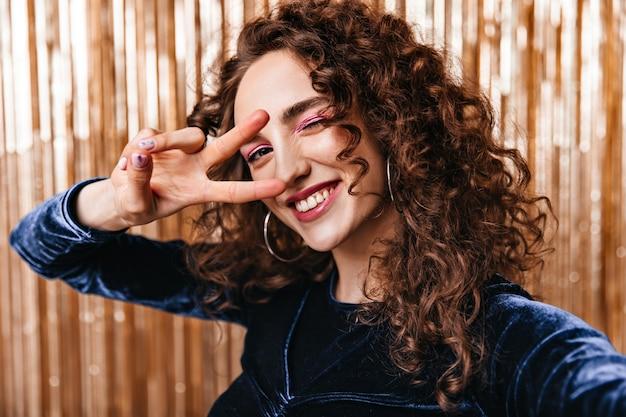 Merveilleuse Dame En Haut Bleu Foncé Montrant Le Signe De La Paix Et Prenant Selfie Photo gratuit