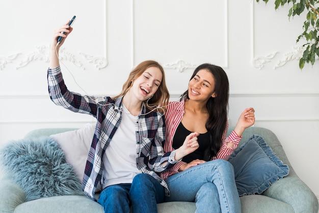 Mesdames assises et écoutant de la musique depuis un téléphone Photo gratuit