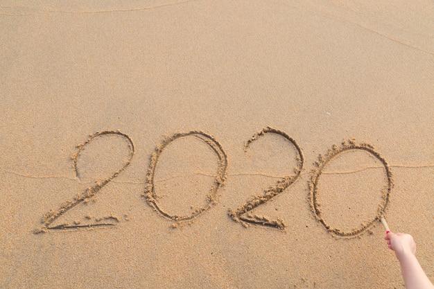 Message abstrait année 2020 écrit sur fond de sable de la plage Photo Premium