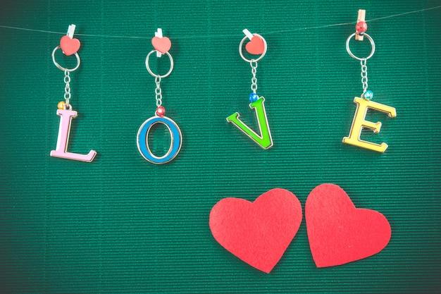 Message d'amour avec 2 coeurs rouges accrocher sur fond vert, concept de la saint-valentin Photo Premium