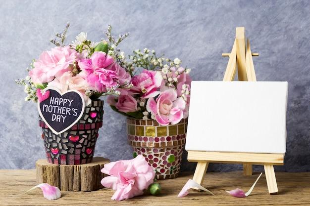 Message de fête des mères sur coeur de bois et fleurs d'oeillets roses dans un pot de fleur de mosaïque Photo Premium