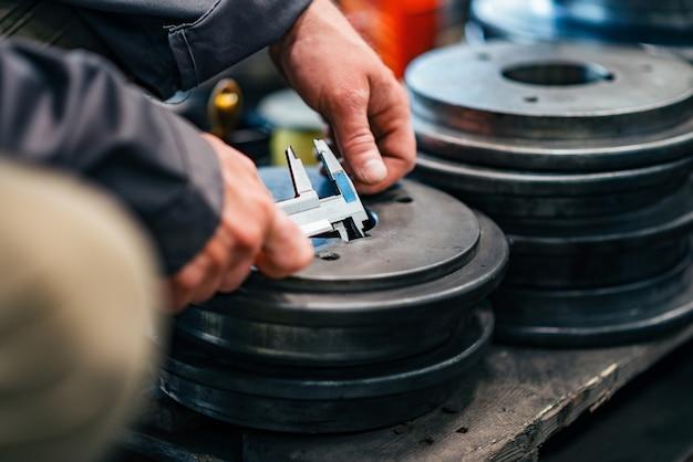 Mesure de pièces métalliques pour trains avec pied à coulisse, gros plan. Photo Premium