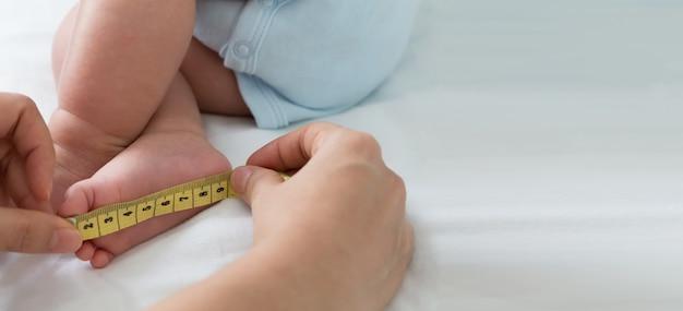 Mesurer la taille du pied bébé. trois mois Photo Premium