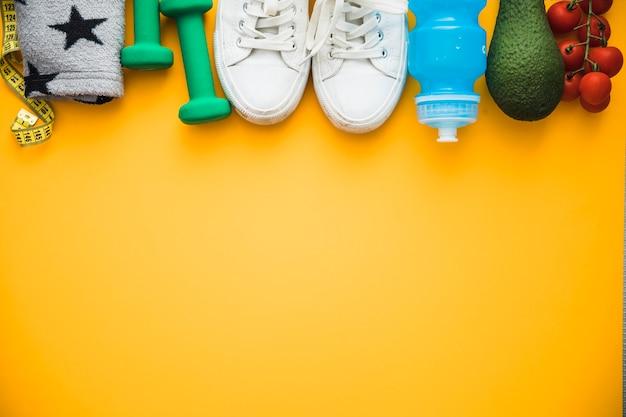 Mètre ruban; brassard; des haltères; chaussures; bouteille d'eau avocat et tomates cerises sur fond jaune Photo gratuit