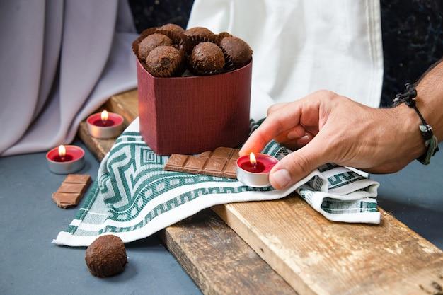 Mettre des bougies enflammées autour d'une boîte de chocolat sur un morceau de bois Photo gratuit