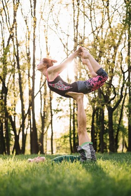 Mi homme adulte, équilibrage femme sur sa jambe pendant l'exercice Photo gratuit