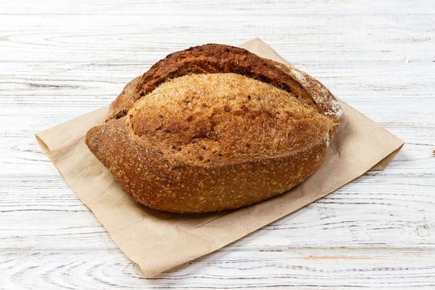Miche de pain de blé frais cuit au four sur une vieille table en bois Photo Premium