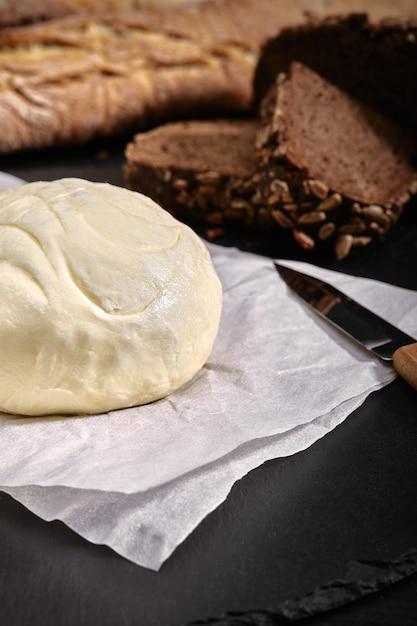 Miche De Pain Avec Du Beurre Et Du Couteau Table Noire, Vue Latérale Photo Premium