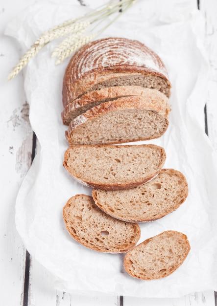 Miche de pain fraîchement sorti du four avec des morceaux sur une planche en bois blanche Photo Premium