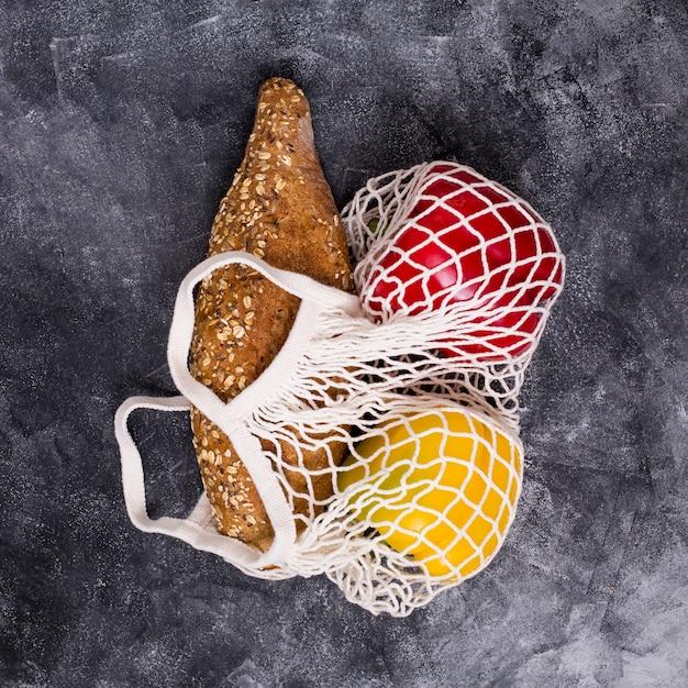 Miche de pain; poivron rouge et jaune dans un sac en filet blanc sur un fond texturé Photo gratuit
