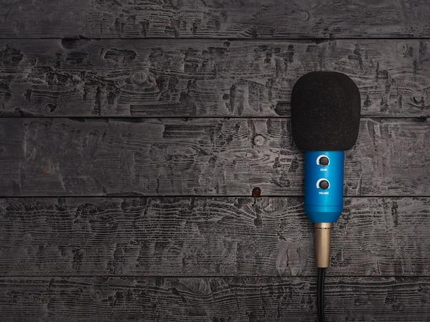 Microphone bleu avec fil sur une table en bois noire. Photo Premium