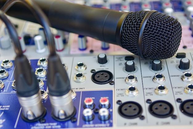 Microphone sans fil agrandi sur fond de mélangeur audio. Photo Premium