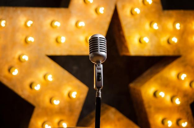 Microphone sur la scène de théâtre ou de karaoké, étoile lumineuse dorée sur fond Photo Premium
