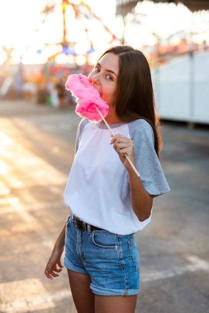 Mid shot femme mangeant barbe à papa rose Photo gratuit