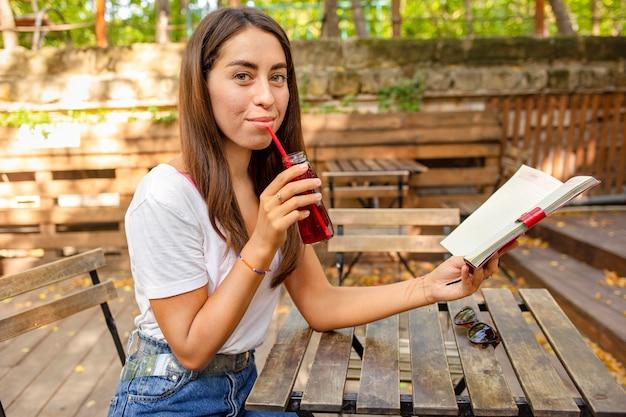 Mid Shot Girl Avec Livre Et Bouteille De Jus De Fruits Frais Photo gratuit