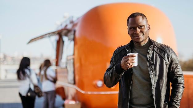Mid Shot Man Holding Coffee Cup En Face De Food Truck Photo gratuit
