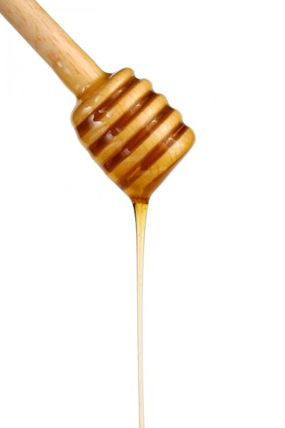 Miel coulant d'un bâton en bois Photo Premium