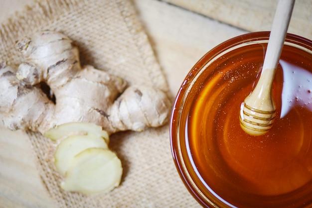 Miel dans un bocal avec une louche au miel et au gingembre sur un sac en bois Photo Premium