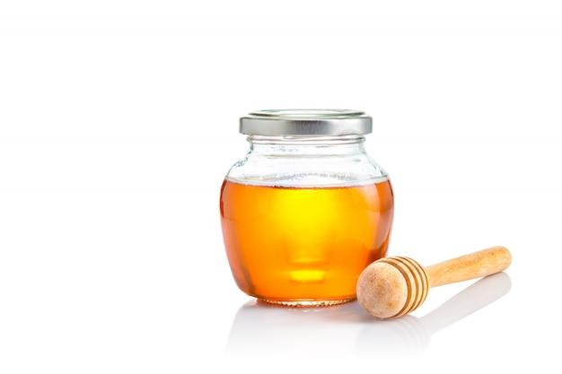 Miel dans un bocal en verre à couvercle fermé avec une louche en bois sur le côté, le tout sur fond blanc Photo Premium