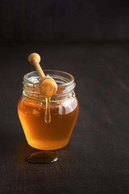 Miel dans un bocal en verre avec une louche de miel sur fond de table en bois rustique. espace de copie. Photo Premium