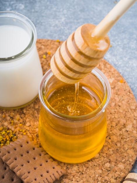Miel dégoulinant de goutteur dans un pot de verre avec du lait et des biscuits sur des caboteurs de liège Photo gratuit