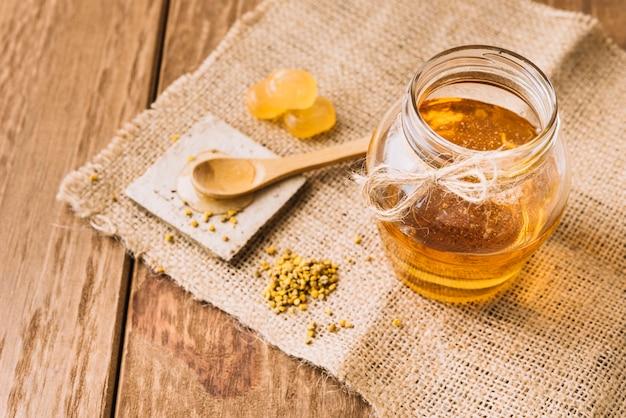 Miel doux; graines de pollen d'abeille et bonbons sur toile de sac Photo gratuit