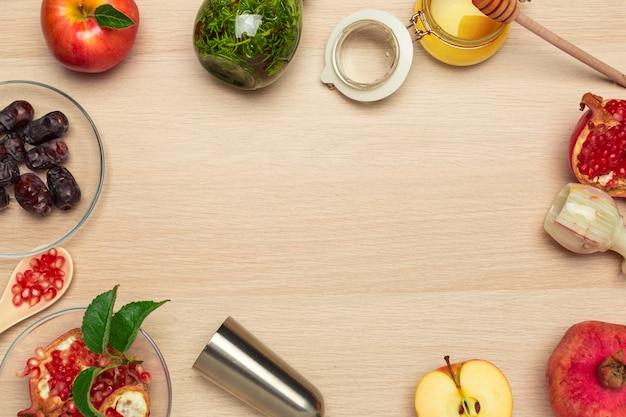 Miel, grenade, pomme et dates sur une planche de bois. nouvel an juif rosh hashana célébration Photo Premium