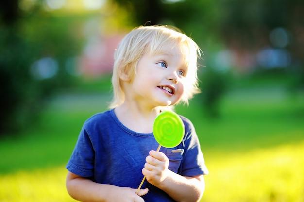 Mignon bambin avec grosse sucette verte. enfant mangeant des friandises sucrées. bonbons pour les jeunes enfants. plaisirs d'été en plein air Photo Premium