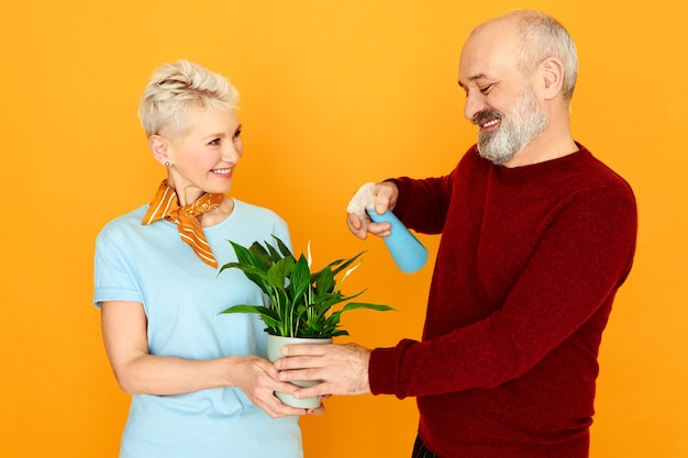 Mignon Charmant Couple De Personnes âgées Prenant Soin De La Plante D'intérieur Ensemble. Heureuse Belle Femme Mature Tenant Une Fleur En Pot Tandis Que Son Mari Barbu Hydrate Ses Feuilles Vertes à L'aide D'un Vaporisateur Photo gratuit